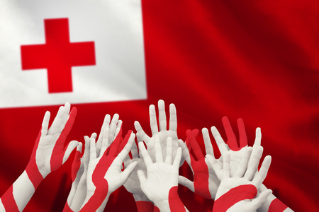 People raising hands in the air against close-up of tongan flag