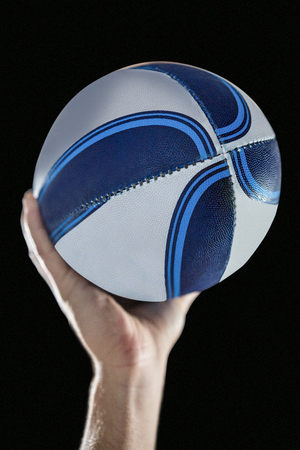 cropped out: Close-up of of rugby player with arm raised holding ball against black background Stock Photo