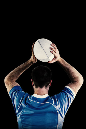turned out: Rugby player about to throw a rugby ball against black