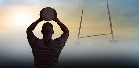 pelota rugby: Vista trasera del deportista de lanzamiento pelota de rugby contra puestos metas Foto de archivo