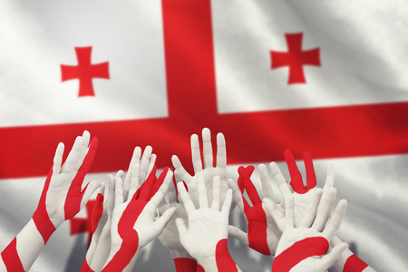 raise the white flag: People raising hands in the air against georgian flag with red cross symbols