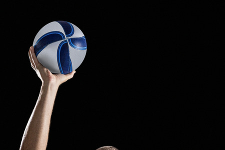 cropped out: Cropped image of rugby player with arm raised holding ball against black background Stock Photo