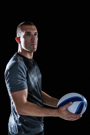 cut the competition: Serious rugby player looking way while holding ball against black background