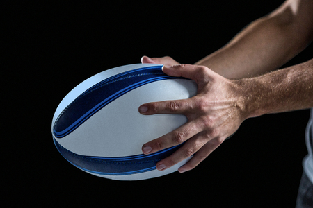cropped out: Cropped image of sports player holding ball against black background