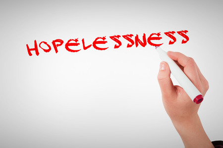 hopelessness: The word hopelessness against businesswomans hand writing with marker