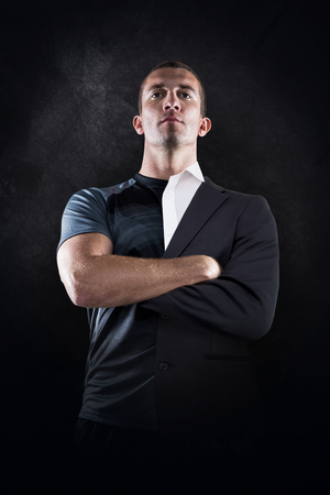 half dressed: Confident rugby player with arms crossed against half a suit
