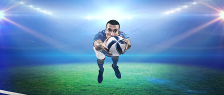 player: Portrait full length of American football player diving against rugby stadium Stock Photo