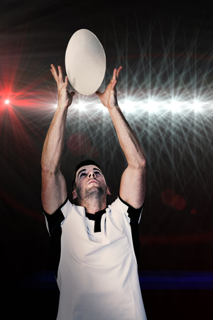 catching: Rugby player catching the ball against spotlights