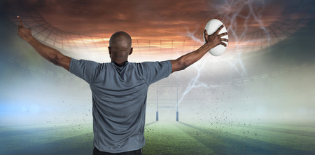 winning pitch: Rear view of sportsman with arms raised holding rugby ball against rugby pitch