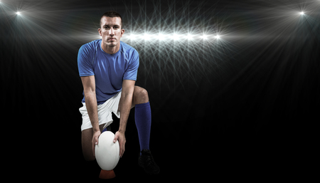by placing: Full length portrait of rugby player placing ball against spotlight