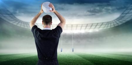 and rugby ball: El jugador de rugby a punto de lanzar una pelota de rugby contra el estadio de rugby Foto de archivo