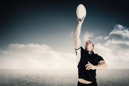 pelota rugby: El jugador de rugby atrapar una pelota de rugby contra el paisaje del desierto