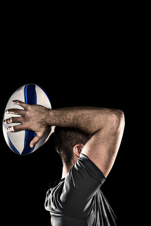 sportsperson: Rugby player throwing ball against black