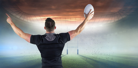 winning pitch: Rugby player celebrating with the ball against rugby pitch