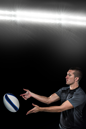 catching: Rugby player catching ball against spotlight Stock Photo
