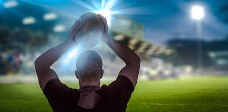and rugby ball: El jugador de rugby a punto de lanzar una pelota de rugby contra la cancha y gradas