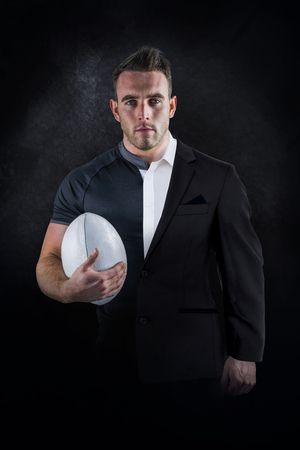 half ball: Tough rugby player holding ball against half a suit