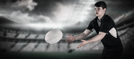and rugby ball: Rugby player throwing a rugby ball against rugby arena