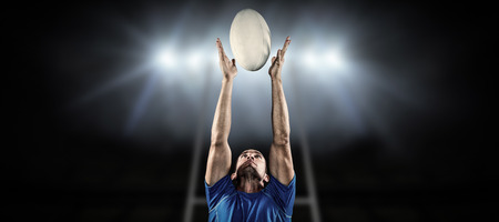 blue spotlight: Rugby player catching ball against rugby stadium