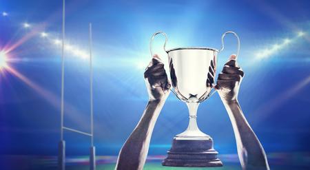 trofeo: Mano cosechada de atleta sosteniendo el trofeo contra el estadio de rugby