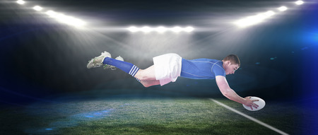 scoring: A rugby player scoring a try against rugby stadium