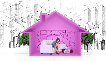 taking off: Cute woman sitting on couch taking off her shoes against house shape with kitchen sketch