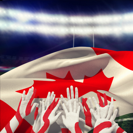 winning pitch: People raising hands in the air against rugby stadium Stock Photo