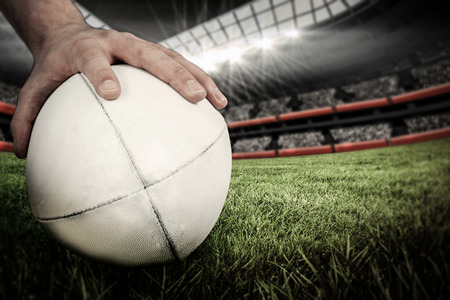 rugby ball: A rugby player posing a rugby ball against rugby stadium Stock Photo