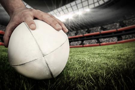 pelota rugby: Un jugador de rugby que representa un balón de rugby contra el estadio de rugby Foto de archivo