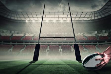 pelota: Primer plano de los deportes del jugador que sostiene la bola contra el campo de rugby Foto de archivo
