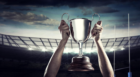 lift hands: Successful rugby player holding trophy against rugby stadium Stock Photo