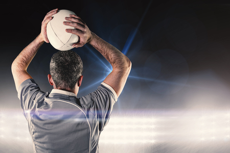 rugby ball: Rugby player about to throw a rugby ball against spotlights Stock Photo