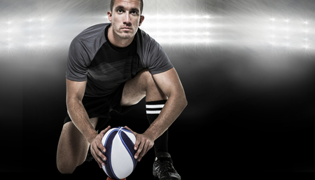 player: Portrait of rugby player in black jersey placing ball against spotlight Stock Photo