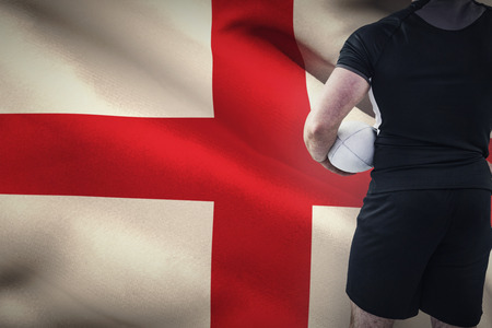 rugby: Rugby player holding the ball against england flag against white background