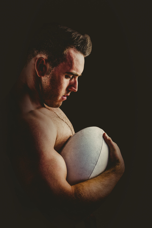 tricep: Shirtless rugby player holding ball on white background Stock Photo