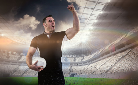 winning pitch: Rugby player cheering with the ball against rugby stadium