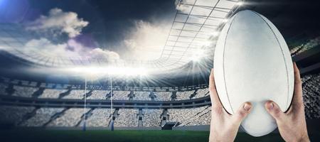 pelota rugby: El jugador de rugby atrapar una pelota de rugby contra el estadio de rugby Foto de archivo