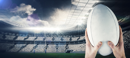 rugby ball: Rugby player catching a rugby ball against rugby stadium Stock Photo