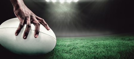 rugby: Cropped image of sportsman holding rugby ball against rugby stadium