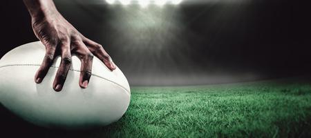 and rugby ball: Recorta la imagen de deportista bola celebraci�n de rugby contra estadio de rugby Foto de archivo