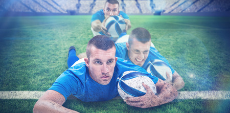 world player: Rugby player looking away while lying in front with ball against rugby pitch