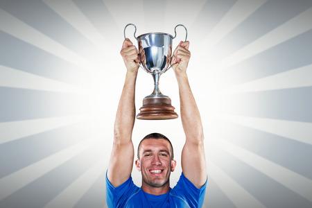 trofeo: Retrato de la sonrisa, tenencia, trofeo jugador de rugby contra el diseño lineal Foto de archivo