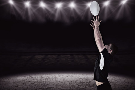 and rugby ball: Rugby player catching a rugby ball against spotlight and pitch