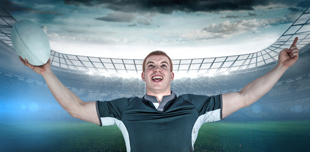 winning pitch: A rugby player gesturing victory against rugby stadium