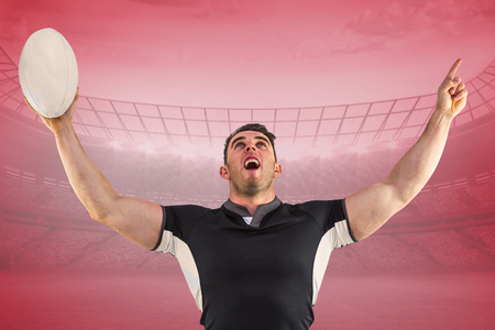 winning pitch: Rugby player cheering with the ball against red vignette