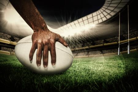 Rugby ball: Primer plano de jugador de los deportes que sostiene la bola contra el campo de rugby