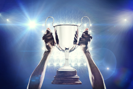 sports winner: Cropped hand of athlete holding trophy against spotlights Stock Photo