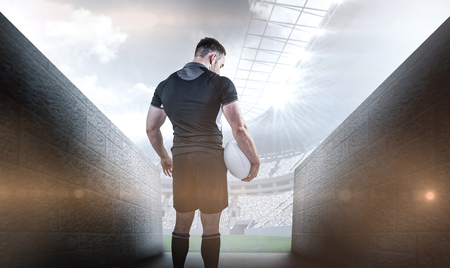 stadium crowd: Tough rugby player holding ball against rugby stadium