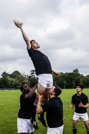teammates: Rugby players jumping for line out at the park