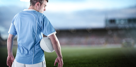 and rugby ball: Rugby player holding a rugby ball against pitch